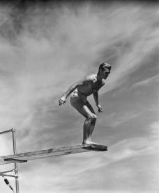 Man standing on springboard, preparing to dive, (B&W)